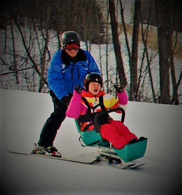 Man Pushing Girl in Chair Ski